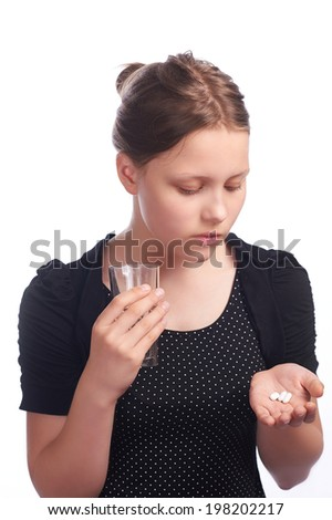Teen girl with a pill and water - stock photo