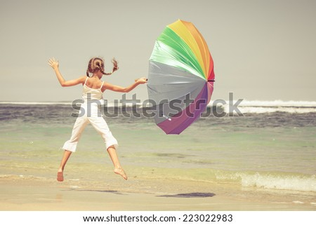 teen girl with an umbrella  jumping on the beach at blue sea shore in summer vacation at the day time - stock photo
