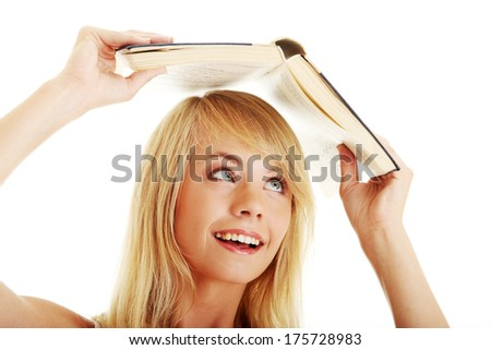 Teen girl with book over her head, isolated on white - stock photo