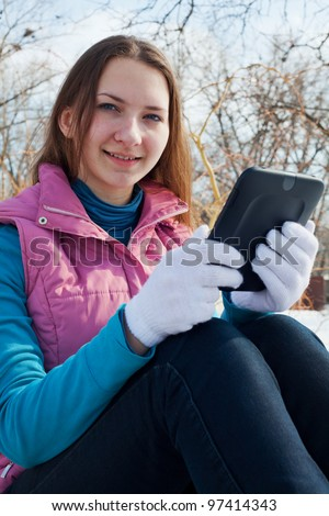 Teen girl with e-book reader in a park at winter time - stock photo