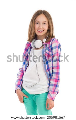 Teen girl with headphones on her neck. Young girl in lumberjack shirt and green trousers posing. Three quarter length studio shot isolated on white. - stock photo