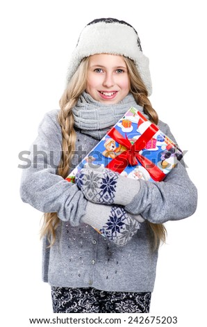 Teen girl with long braids in warm hat and mittens keeping the gift - stock photo