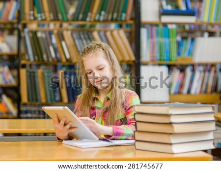 Teen girl with tablet computer working in library - stock photo