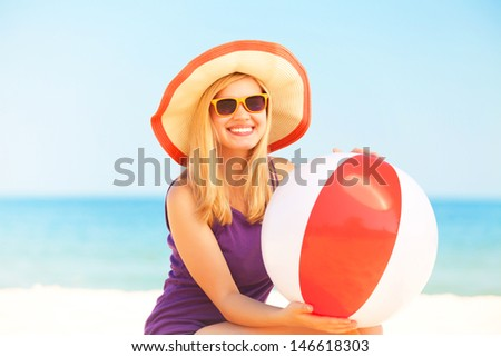 Teen girl with toy ball at the beach. - stock photo