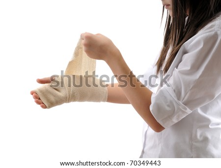 Teen girl wrapping her hand with a bandage isolated on white background - a series of MEDICAL images. - stock photo