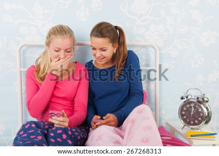 Teen girls in pajama sitting on bed having fun with their smartphone - stock photo
