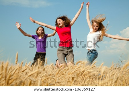 Teen girls jumping at a wheat field in a sunny day - stock photo