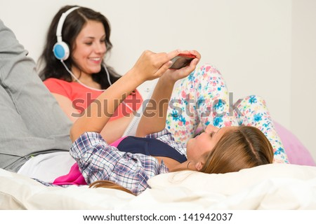 Teen girls relaxing on bed with mobile phone and headphones - stock photo