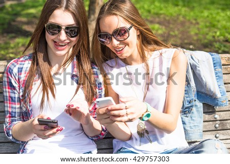 Teen girls using their phones. Young happy teenagers having fun in summer park. - stock photo