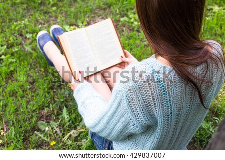 Teen happy girl read a book in city park outdoor - stock photo