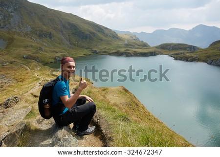 Teen hiker sitting on a rock near a mountain lake - stock photo