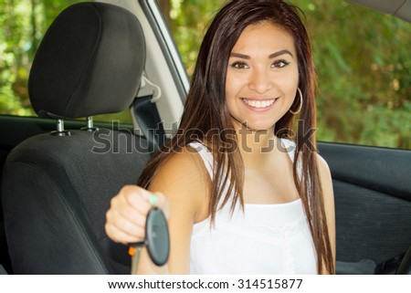 Teen holding up keys to her new car - stock photo