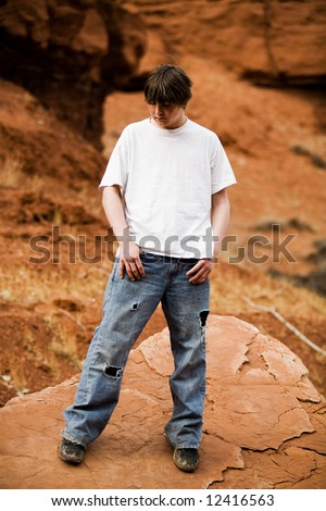 Teen in nature, in wilderness area standing on large flat rock - stock photo