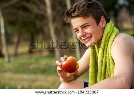 Teen jogger eating apple after exercise outdoors. - stock photo