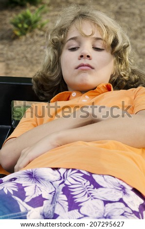 Teen laying back relaxing on a park bench - stock photo