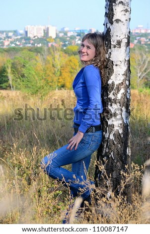 Teen leans against a birch and smile - stock photo