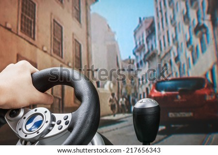 Teen playing in the race behind the wheel of a game console  - stock photo