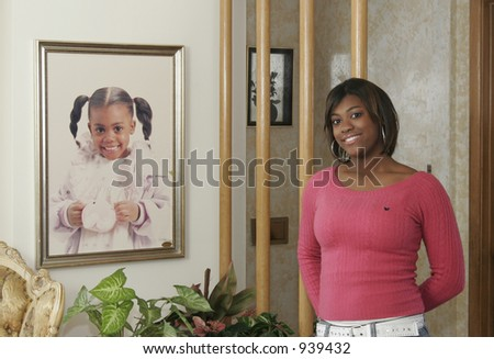teen posing next to portrait as child - stock photo