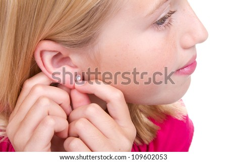 teen putting in earring isolated on white - stock photo