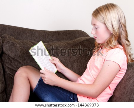 teen reading a book while relaxing or sitting on couch - stock photo