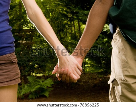 Teen romance - Caucasian girl, African American boy holding hands - stock photo