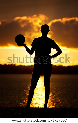 Teen Volleyball Girl Poses Silhouette Lake Background - stock photo