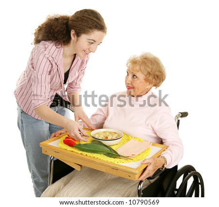 Teen volunteer brings a meal to an elderly woman in wheelchair.  Isolated on white. - stock photo