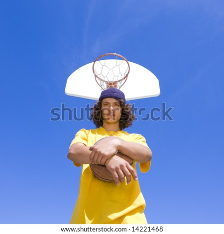 Teen with basketball below hoop - stock photo