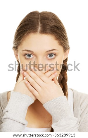 Teen woman covering her mouth. - stock photo