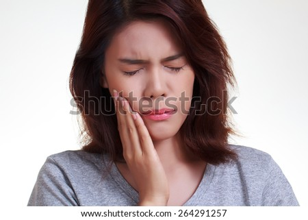Teen woman pressing her bruised cheek with a painful expression as if she's having a terrible tooth ache. - stock photo