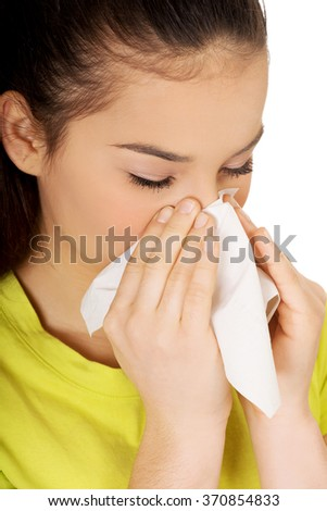 Teen woman sneezing to tissue. - stock photo