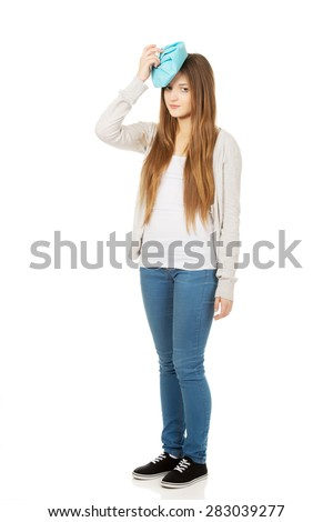Teen woman with headache and ice bag. - stock photo