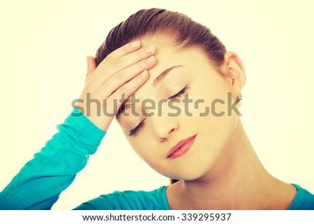 Teen woman with headache holding her head. - stock photo