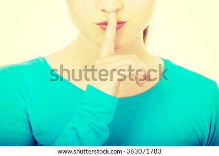 Teen woman with hush gesture. - stock photo