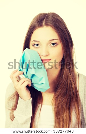 Teen woman with toothache and ice bag. - stock photo