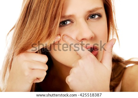 Teenage angry woman poping pimple - stock photo