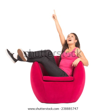 Teenage Attractive Girl Sitting On Red Armchair Pointing Up Isolated On White - stock photo