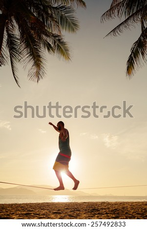 teenage balancing on slackline with sea view on the beach sunrise silhouette - stock photo