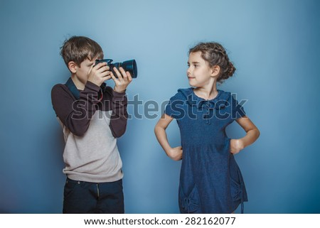 Teenage boy about seven years old girl photographed on a professional camera on gray background, smiling, model, pose - stock photo