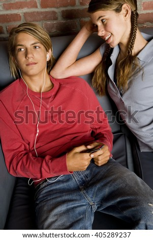 Teenage boy and girl seated, boy listening to music on mp3 - stock photo