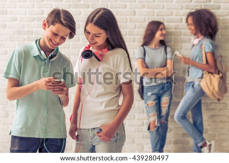Teenage boy and girl with headphones are using smartphone, talking and smiling, two girls are talking in the background - stock photo