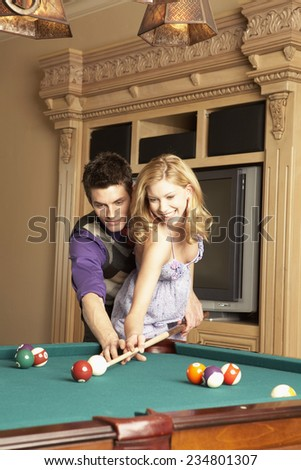 Teenage Boy Assisting Girl at Pool Table - stock photo