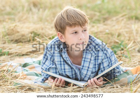Teenage boy dreaming reading a book outdoor - stock photo