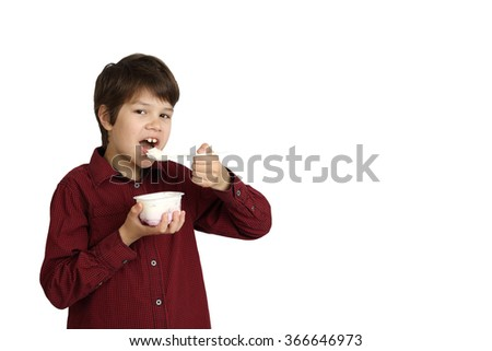 Teenage boy eats yogurt isolated on white background with copy space for text or advertising - stock photo