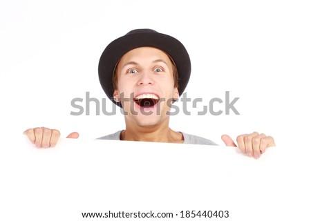Teenage boy hiding behind a billboard - stock photo