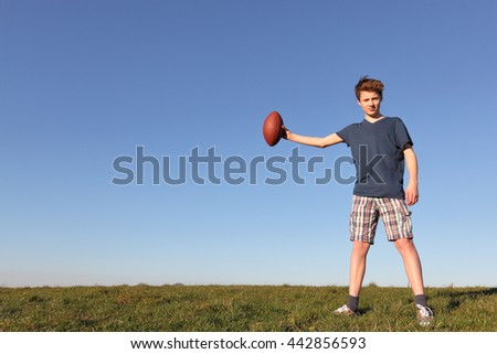 Teenage boy holding a football outside in a meadow - stock photo