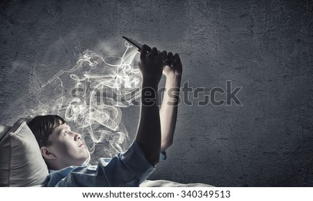 Teenage boy in pajamas lying in bed using tablet pc - stock photo