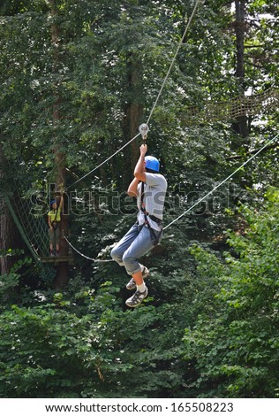 Teenage boy is moving down at the rope parkour outdoors. She is photographed against the green forest. - stock photo