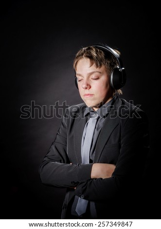 Teenage boy listening music in headphones isolated on black background - stock photo
