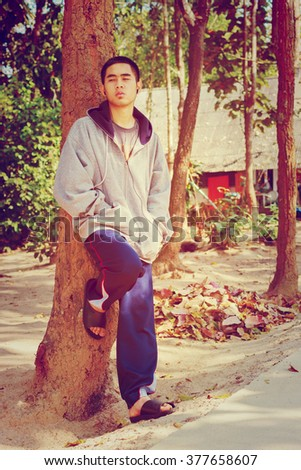 Teenage boy listening to mp3 outdoors, Vintage style - stock photo